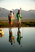 Two Masai tribesmen standing at the edge of infinity pool, Namunyak, Matthews Mountains, Kenya