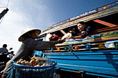Woman offering food for sale on board ferry crossing the Mekong river, Si Phan Don in southern Laos