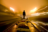 Man standing on barge going along the canal on a foggy night, London, England
