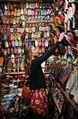 A woman browsing for shoes in a market stall in the souk, Shopping in the Medina, Marrakesh, Morocco.
