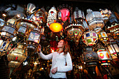 Young woman browsing for Moroccan lanterns in a market stall in the souk, Shopping in the Medina, Marrakesh, Morocco.