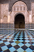 View across an ornamental pool at an arch in a courtyard at Ali Ben Youssef Medresa, Marrakesh, Morocco, Marrakesh, Morocco.