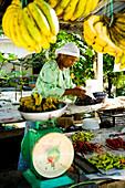 Fruit seller weighing out bananas, Terengganu, Malaysia