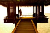 Woman on stilted hut over sea at sunset, Maldives