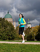 One young woman jogging on the Freundschaftsinsel, look over the Old City Hall on the Alter Markt, St. Nicholas Church, Brandenburg, Germany