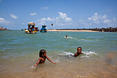 Children play in water at Olinda beach with teenagers jumping from fishing boats, Olinda, near Recife, Pernambuco, Brazil, South America