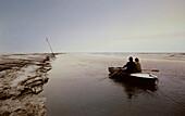 Two men in a rowboat in a tidal creek, East Frisian Wadden Sea, East Friesland, North Sea, Lower Saxony, Germany, Europe