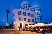 Restaurant terrace,  buildings and Rheinturm tower in the evening, Neuer Zollhof, Media harbour, Duesseldorf, Rhine river, North Rhine-Westphalia, Germany, Europe