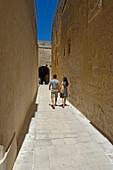Couple walking along narrow passage, rear view, Midina, Malta