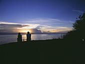 Couple having sundowner drinks at sunset on Domwe Island, Lake Malawi, Malawi