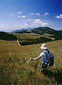Walker trekking through meadows on top of the Zomba plateau, Malawi