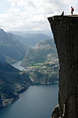 Two people standing on edge of Pulpit Rock, Preikestolen, above Lysefjorden, Norway