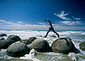 Woman leaping between two of the Moeraki Boulders, South Island, New Zealand