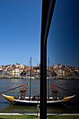 A view of the city of Oporto partly reflected on a glass window, Portugal