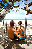 Tourists sitting on swing at Red Frog Beach, Bocas del Toro, Caribbean, Panama