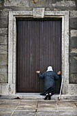 An old lady kneels in worship at the door of the Church, Muxia, Galicia, Spain