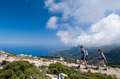 Two hikers on track towards Teix peak, side view, Majorca, Ballearic Islands, Spain, track built by Archduke Ludwig Salvador