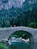 Two walkers crossing bridge at Bujarelo near Torla village, Pyrenees, Aragon, Spain.