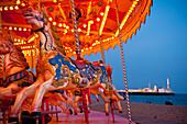 Merry-go-round on Brighton beach at dusk, Brighton, East Sussex, UK.