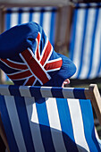 Man in Union Jack hat in sunchair, Skegness, Linconshire, England, UK