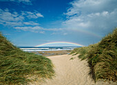 Looking through gap in dunes to double rainbow, Embleton Bay beach near Dunstanburgh Castle, Northumberland, England