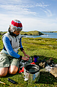 Young woman preparing picnic, Outer Hebrides, Scotland