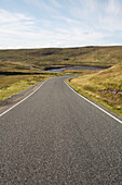 Empty single lane road through hills, Yell, Shetland Islands