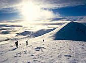 Hikers on a mountaintop in the snow, Stob coire nan Easain, Scotland