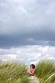 Woman reading on beach, Chichester, West Sussex, United Kingdom