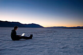 Man using laptop on the salt pans at dawn, Death Valley, California