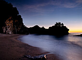 Looking out to sea at dusk from small beach with McWay Waterfall at end, Julia Pfeiffer State Park, Big Sur, California