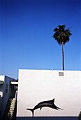 Swordfish mural on a pink building with palm tree, Palm Springs, California