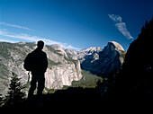 Silhouette of hiker looking towards Half Dome and the Yosemite Valley, Yosemite National Park, California