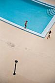 Children (10-11) walking around swimming pool, elevated view, Jupiter, Florida, USA