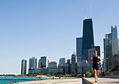 Man jogging on lakefront path along Oak Street Beach, Chicago, Illinois, USA