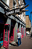 A man walks past a crocodile shaped sign for Gumbofile, a cafe bar, in the French Quarter, New Orleans, Louisiana, USA