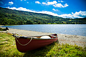 'Canoes/ kayaks available for families to rent, to be used in the river and lake. Nant Gwynant Lake glistening in the sun, Llyn Gwynant Campsite, Nantgwynant, Snowdonia National Park, North Wales