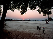 People on walking safari across dry river bed at dusk, South Luangwa National Park, Zambia