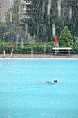Swimmer swimming during heavy rainfall, Freibad Spiesel, Aalen, Schwaebische Alb, Baden-Wuerttemberg, Germany