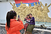 Young people of Laos posing for photo in front of a communist monument, Sam Neua, Highland Laos