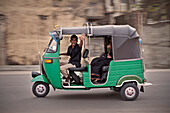 Local Tuk Tuk driver waves hello out of his three wheeler while passing by, capital Colombo, Sri Lanka