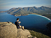Hiker enjoys view from a rock at Mt Amos at Wineglass Bay, beach, Freycinet National Park, Tasmania, Australia