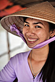 Vietnamese woman with hat smiles while being portraited, Mekong Delta, Vietnam