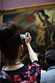 France, Paris, Musee du Louvre museum, 19th century French painting gallery, visitors photographing the painting Liberty Leading the People by Delacroix