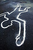 Chalk outline of body drawn on the floor as if at a crime scene
