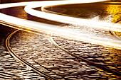 city, cobble, cobblestones, curve, Czech, dusk, light, headlights, metal, pattern, paving, perspective, Prague, rain, reflection, republic, road, roadway, stone, street, surface, track, tram, tramway, wet. city, cobble, cobblestones, curve, Czech, dusk, l