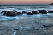 Moeraki boulders at dusk, glow over Pacific Ocean, near Oamaru, Otago, New Zealand