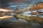 Blue Lake reflections of clay cliffs at sunset, after winter storm and snowfall, St Bathans, Central Otago, New Zealand