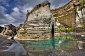 Cliff detail and reflection of algae colours in black sand beach, Tongaporutu, North Taranaki