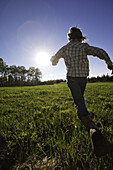 Young Girl in Jeans and Plaid Shirt  Running in Grass Field, Rear View, Oak Creek, Colorado, USA